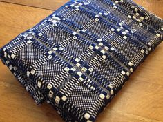 This antique overshot woven coverlet has a hand stitched center seam where the two loomed strips were connected. The colors are dark indigo blue and