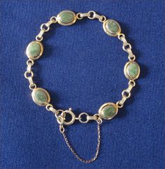 This is a genuine jade bracelet from the Lady Coventry line by Sarah Coventry. It features six pretty green oval cabochon stones that are