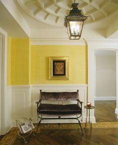 Beautiful detail in the ceiling treatment...wainscoting, crown molding, and door surround are very interesting. And that yellow! Very welcoming..............