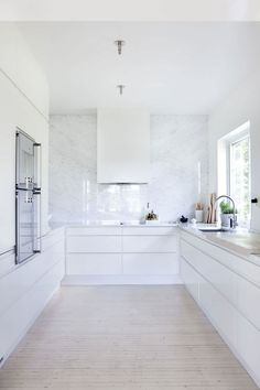 Cucina moderna ed elegante con lungo mobile ad U. Bellissimi dettagli: top e paraschizzi in granito chiaro e parquet in legno a listone molto sottile.