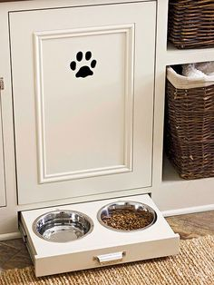 source: BHG    Pet lovers kitchen with all-in-one pet station! A sliding toe-kick drawer built into the base if the kitchen cabinets offers pull out feeding bowls for pets. The ivory painted raised panel cabinets a monogrammed with a black paw print above the pull out bowls. A cubby with rattan storage baskets holds other pet essentials. The tiles floors are layered with a woven jute rug.