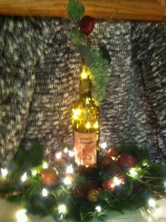Carmela Vineyard has changed to Crossings so these bottles will never be seen again. This bottle light is Carmela wine with a horsefly label sitting in an arrangement of greenery, fruit and pine cones. The bottle light has potpourri and lights inside with vines, grapes, leaves and flowers at the top.