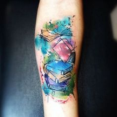 This colorful stack of books. Another amazing book tattoo design on the list is the colorful stack of books, with the alphabets flying.