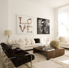 Cool and modern living room space! Modern walnut coffee table, modern tufted chocolate brown velvet chairs with chrome steel base legs. Sleek cream sofas with fluffy throw pillows and a fluffy flokati rug! Love the white cream gourd lamp and white cream paint walls! White paint wall color! White, tan, brown, and beige living room colors.