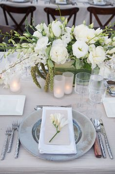 Textured silver cutlery, white linen napkins and fresh white blooms are gorgeous for an outdoor spring wedding celebration.