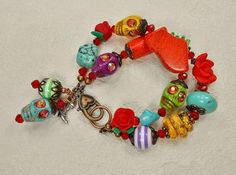 Two strand multicolor cowgirl bracelet is hand created using howlite sugar skull beads in colors of green, turquoise, yellow, and purple. Eyes are embellished with AB pink crystals. Various other howlite beads in yellow, green turquoise and orange are use