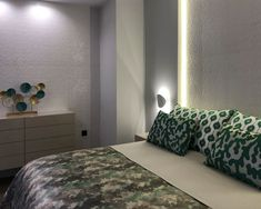 Dormitorio matrimonio moderno. Cabecero realizado en revestimiento porcelánico imitación papel adamascado. Luz indirecta mediante led lineal, y apliques en pared. Cómoda suspendida en dm lacado alto brillo. Proyecto diseñado y coordinado por AZ diseño.