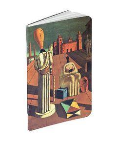 """Llibreta realitzada en motiu de l'exposició """"Somni o realitat. El món de Giorgio de Chirico"""" de CaixaForum Barcelona de juliol a octubre de 2017. La portada reprodueix el quadre """"Muse inquietanti"""", les pàgines són en blanc.  Mida: 10 x 15 cm Material: paper."""