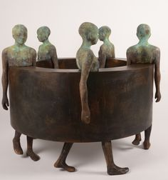 """""""Big Sin Fin III"""": This captivating bronze and steel sculpture by Madrid artist Jesus Curia Perez alludes to the dehumanizing effects that industrialization, automation and robotization are having on society. Here, five human figures are bound to a wheel, much like cogs in a gear. 