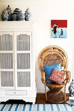 white walls, rattan chair, throw pillows, armoire, chinoiserie, striped carpet