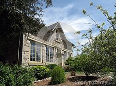 Century, field-stone house with landscaped front yard.