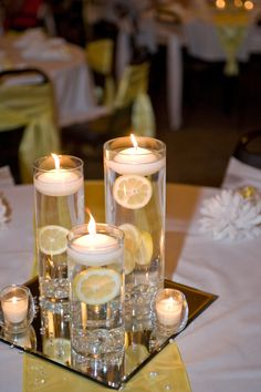 lemon centerpieces. sliced lemons with nuts/bolts looped through fishing wire to hold them in place with floating candles