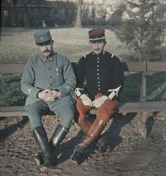 Autochrome stereo slide shows two French soldiers sitting on a bench in front of a large building. It is dated December 1915.