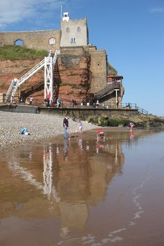 The 'ladder' at Jacob's Ladder beach reflected in the wet sand as the tide comes in. You can see the Clock Tower Cafe perched on the cliff with stunning views over the bay and a walled garden. A fantastic location to enjoy one of the best cream teas in Devon. Sidmouth | East Devon