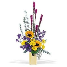 This striking arrangement of yellow, blue and pink flowers will send just the right spark to that special someone. Perfectly suited for a man or a woman. Chrysanthemums, sunflowers, liatris and delphinium delivered in a reflective vase.