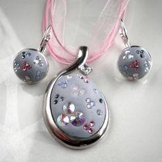 Světle modrá souprava se šatony Swarovski Souprava náhrdelníku a náušnic je zdobena šatony Swarovski v odstínech světle modré a růžové, které jsou zasazeny do bižuterní epoxidové hmoty světle modré barvy. Přívěsek je zavěšen na stužce z organzy a saténové stužce. Délka stužky je cca 43 cm + 4 cm prodlužovací řetízek. Náušnice o průměru 12 mm. Bižuterní ...