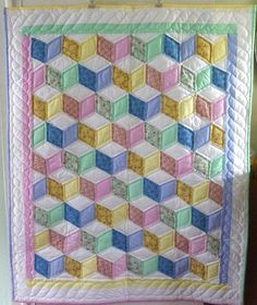 Amish made Tumbling Blocks baby quilt. A difficult to make and very old Amish quilt pattern. Created using unisex colors and a mix of solid and patterns.