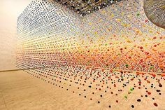 Suspended Bouncy Ball Installation by Nike Savvas    Atomic: Full of Love, Full of Wonder was a 2005 installation by artist Nike Savvas at the Australian Centre for Contemporary Art in Melbourne. The piece involved an immense array of suspended bouncy balls creating a dense field of color in the gallery space that was gently moved in waves by a nearby fan.Savvas most recently exhibited a series of complex geometric thread installations at Breenspace.