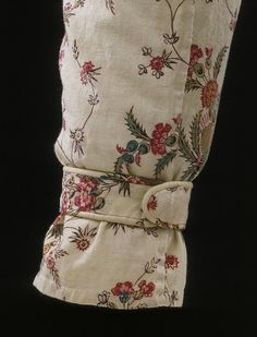 1795-1799: Sleeve on cotton gown.The pattern of floral trails seen on the printed fabric of this gown exhibits a blend of influences from Indian-painted and printed textiles, and woven silks, a style which remained popular until the end of the 18th century.
