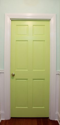 Lime green door at the end of a hall
