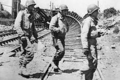 327th troopers, G Company at the Carentan railroad station. Tracks badly hit most likely bt naval bombardment on june 11, 1944.