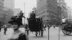 A street view of the Flatiron Building, (Fuller Building), with pedestrian and handsom cabs. This image is a part of a nine minute video, that filmed life in New York City, in the year c.1911. The video can be seen via the Museum of Modern Art (MoMA) website.