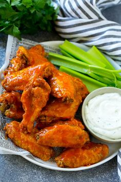 A pile of baked buffalo wings with celery sticks and ranch dressing.