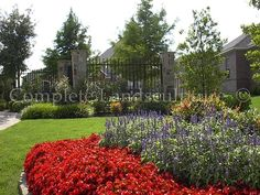 Extremely colorful flower bed with stonework columns and metal fencing