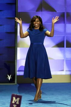 JULY 25, 2016 The First Lady takes the stage at the Democratic National Convention in a blue cap-sleeved, belted Christian Siriano dress with silver pumps and pearl-accented hoop earrings.