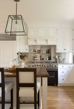 white kitchen + stainless steel backsplash, black range & butcher block island