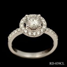 Stunning diamond cluster in 18ct white gold. This eye-catching ring comprises of a 1.24ct round cut centre stone, 4 claw set and housed within a pretty diamond circle. The low set mount and narrow, diamond set shank compliment the cluster beautifully making it an enviable piece of jewellery. £4950