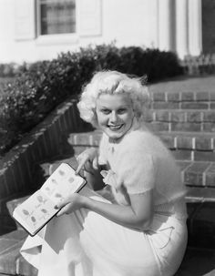Jean Harlow with her book of autographed fingerprints including those of Joan Crawford and Clark Gable, 1934.