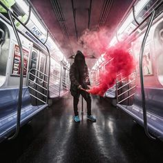 Lighting up a red flare gun inside what appears to be an empty Q train, photographer Dark Cyanide captures his masked friend under a red cloud of smoke. The photographer, 19, admitted what he and his friends do is highly dangerous, illegal, and he does not recommend others attempt to explore such tunnels.