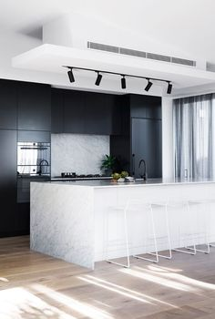 Best Interior Design Ideas : Mixing of Modern and Minimalist Style cool modern kitchen decor idea // track lighting for the ktichen // black stainless appliances // black cabinets // marble wrapped island // minimal modern white stools High End Kitchens, Black Kitchens, Kitchen Black, White Marble Kitchen, Modern White Kitchens, Quirky Kitchen, Diy Kitchens, Bespoke Kitchens, Beautiful Kitchens