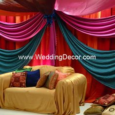 A sangeet/mehndi backdrop in orange, blue and fuchsia with pillow and fabric lantern accents. . To see additional wedding decor pictures please visit our website at www.weddingdecor.com