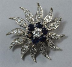 Diamond set sunburst brooch set with a centre brilliant cut diamond (estimated weight approximately 0.35cts.) surrounded by untested round cut sapphires all in hallmarked 18ct. white gold assayed circa 1968. Gross weight 11.4grams.