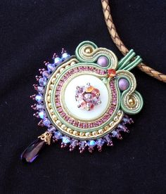 This pendant has a light green Shell center surrounded by soutache in green, gold and purple, with pink rhinestones and lilac Swarovski crystals. Seated on a golden braided leather cord and finished with a cobber lobster clasp. This necklace measures about 20 inch.