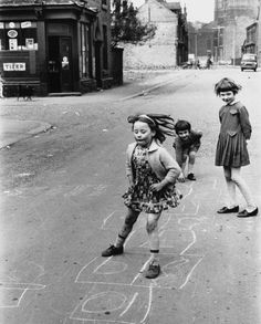 Three girls play hopscotch in the middle of the street in 1968