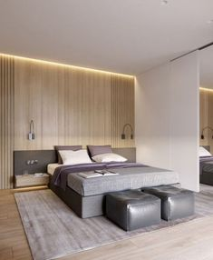 a modern space with light colored wooden wall and floor, an upholstered grey bed with a headboard and grey leather poufs