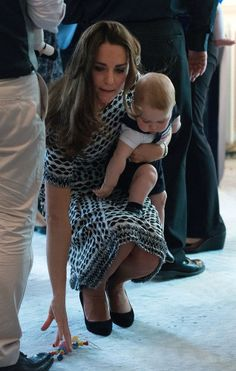 Catherine (C), the Duchess of Cambridge, holds Prince George (R) as she picks up a toy he dropped during a Plunket nurse and parents group visit at Government House in Wellington on April 9, 2014. Plunket is a national not-for-profit organisation that provides care for children and families in New Zealand. Britain's Prince William, Kate and their son Prince George are on a three-week tour of New Zealand and Australia.    AFP PHOTO / POOL / MARTY MELVILLE        (Photo credit should read ...