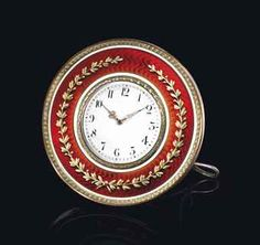 FABERGÉ A SILVER-GILT AND TWO-COLOUR GOLD-MOUNTED ENAMEL DESK CLOCK, WORKMASTER'S MARK OF HENRIK WIGSTRÖM, ST PETERSBURG, 1903-1908. Circular, enamelled in translucent scarlet red over a wavy guilloché ground, centering a white enamel dial within a green gold laurel bezel, black Arabic chapters and pierced rose gold hands, the body applied with a ribbon-tied berried laurel within white champlevé enamel bands, with green gold acanthus-chased border.