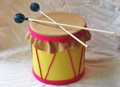 Coffee can drum craft! DIY Here's what u need... Aluminum coffee can with plastic lid 2 sheets yellow construction paper 1 sheet tan felt ½ sheet magenta felt Magenta yarn 1 rubber band Scissors Glue stick White craft glue 2 wooden dowels 2 small foam balls Blue yarn