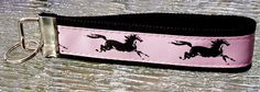 """This listing is for a 6"""" long key fob made of high quality grosgrain ribbon and heavy-duty cotton webbing.  It has a nickel fob tip and split ring.  The ribbon is light pink with black galloping horse"""