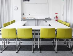 Conference room with green chairs and white tables