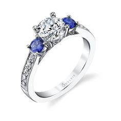 Lola – Three Stone Sapphire Engagement Ring – This romantic three stone engagement ring features a 1 carat round brilliant diamond center with an exquisite deep blue sapphire on each side. The total weight of the ring is carats. Engagement Ring Buying Guide, Three Stone Engagement Rings, Vintage Engagement Rings, Diamond Engagement Rings, Oval Engagement, Fashion Rings, Thing 1, Just For You, Blue Sapphire