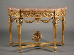 A Louis XVI period  carved and gilt wood console. The semi circular pierced apron is decorated with stylized waves and garlands. The console rests on four legs linked by a...
