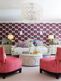 ~love this colorful sitting area~purple patterned accent wall, pink chairs, white chandelier~
