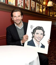 Bradley Cooper held up his brand-new caricature at the legendary Broadway hangout Sardi's restaurant in NYC May 6.