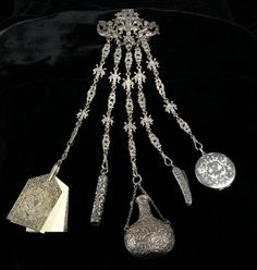 According to Wikipedia, a chatelaine is a chain or series of chains worn by a woman at her waist to hold a variety of useful items like scissors, keys, etc. Chatelaines seem to be at their most popular in the mid-19th century. This is what the head housekeeper on Downton Abbey has on her left side waist