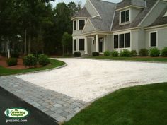 Driveway of crushed sea shells with cobblestone apron.